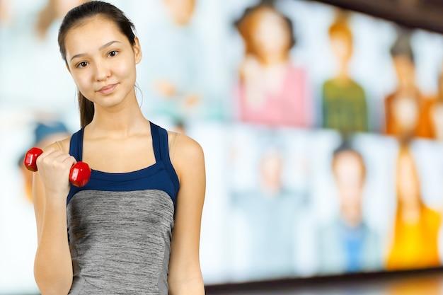 Heureuse femme fitness soulevant des haltères