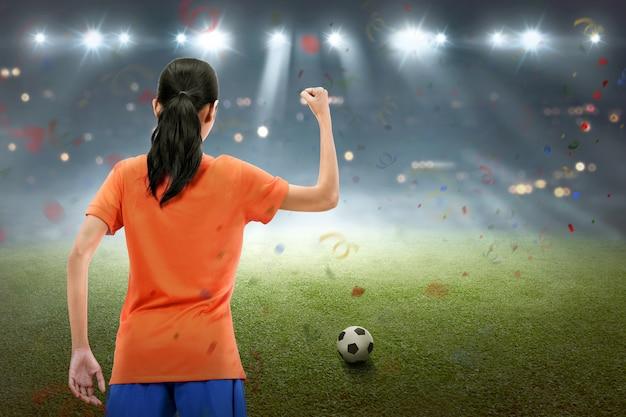 Heureuse femme de footballeur asiatique célèbre la victoire