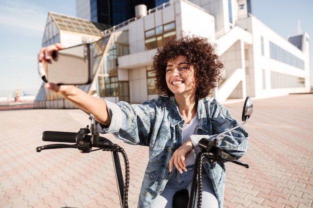 Heureuse femme frisée assise sur une moto moderne à l'extérieur