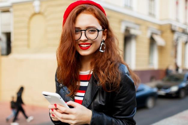 Heureuse femme gingembre fabuleux en élégant béret rouge dans la rue à l'aide de smartphone