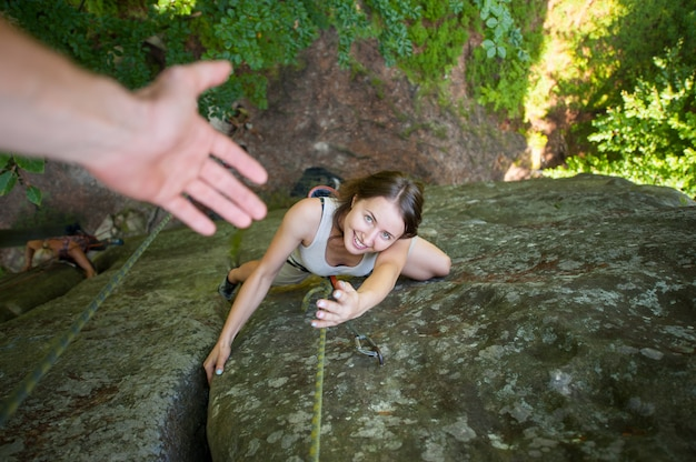 Heureuse femme grimpeur grimpe sur un rocher élevé et tente de prendre un coup de main. vue de dessus