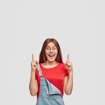 Heureuse femme heureuse avec une expression satisfaite, pointe avec l'index vers le haut, fascinée par quelque chose