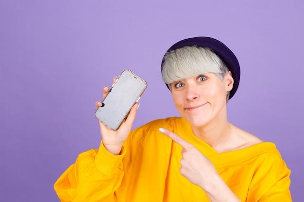 Heureuse femme heureuse pointe avec l'index à l'écran vide, montrant un appareil moderne