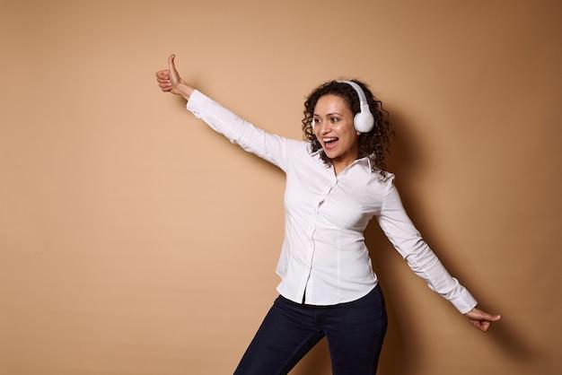 Heureuse femme hispanique aux cheveux bouclés debout avec les bras tendus sur un mur beige tout en écoutant de la musique au casque. copier l'espace