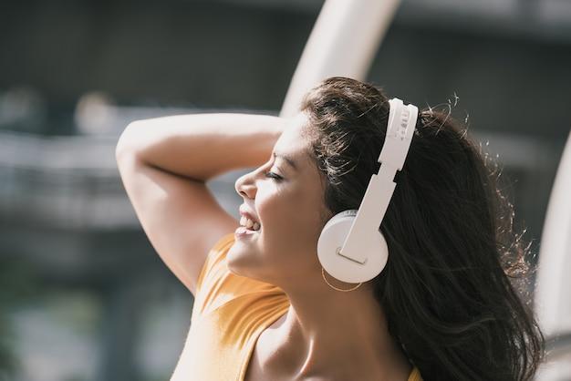 Heureuse femme hispanique portant des écouteurs en écoutant de la musique