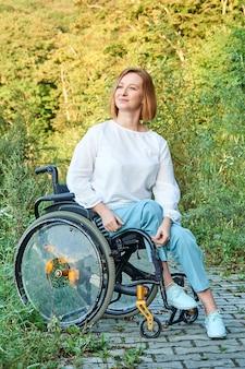 Heureuse femme inclusive aux cheveux roux dans un fauteuil roulant bénéficiant d'un temps ensoleillé à l'automne.