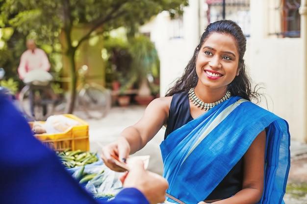 Heureuse femme indienne en sari bleu vendant des légumes dans un marché