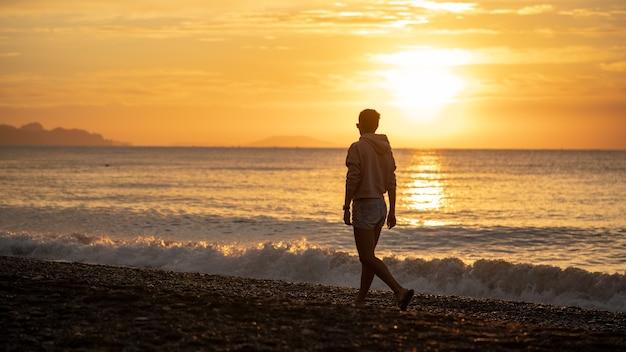 Heureuse femme insouciante profitant d'un beau lever de soleil sur la plage. soleil jaune sur la mer. vagues de couleurs oranges. fond naturel. belle scène sereine. matin.