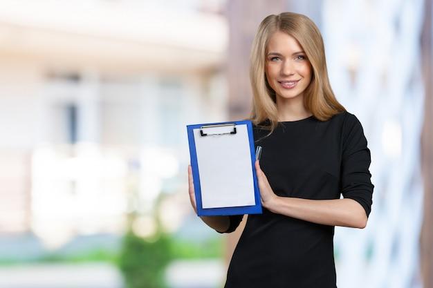 Heureuse femme jeune belle entreprise souriante avec presse-papiers