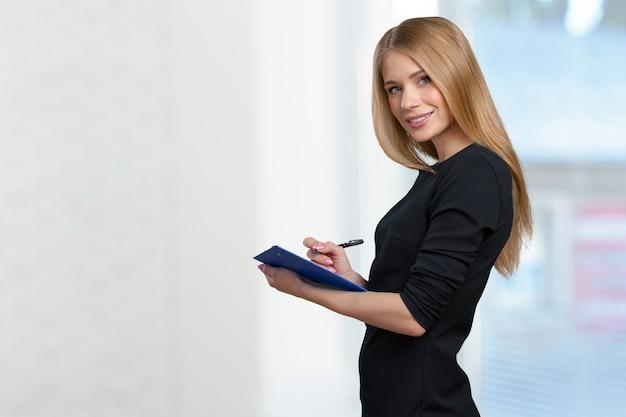 Heureuse femme jeune belle souriante avec le presse-papier