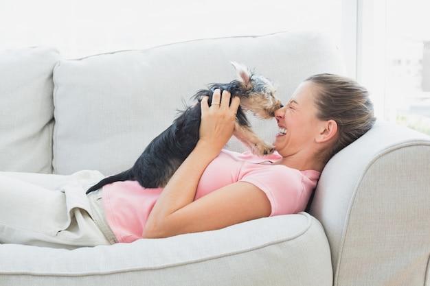Heureuse femme jouant avec son yorkshire terrier sur le canapé