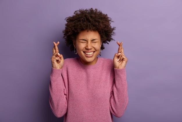 Heureuse femme joyeuse émotive prie dieu pour bonne chance, croise les doigts, sourit largement, montre des dents blanches, porte un pull rose