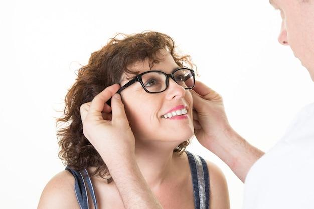 Heureuse femme joyeuse à l'opticien essaie ses nouvelles lunettes