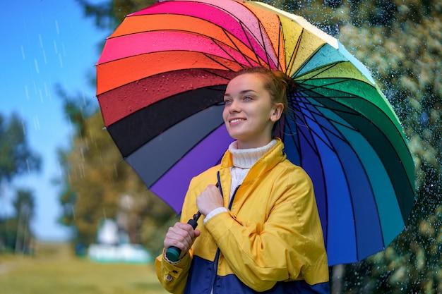Heureuse femme joyeuse avec parapluie arc-en-ciel pendant la pluie par temps de pluie