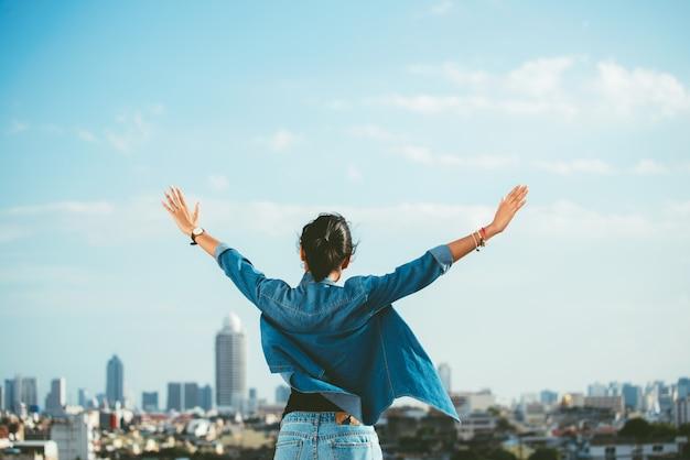 Heureuse femme levant les mains dans le fond de scène de ville avec espace de copie