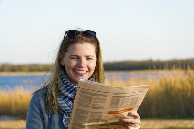 Heureuse femme lisant le journal près du lac, avec un sourire éclatant sur son visage.