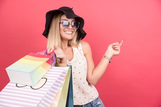 Heureuse femme à lunettes et chapeau tenant ses sacs à provisions.