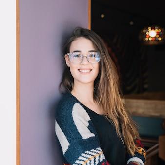 Heureuse femme à lunettes debout au mur