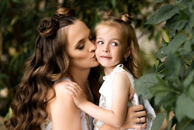Heureuse femme maman joue avec sa fille à l'extérieur dans des robes assorties sur une journée ensoleillée