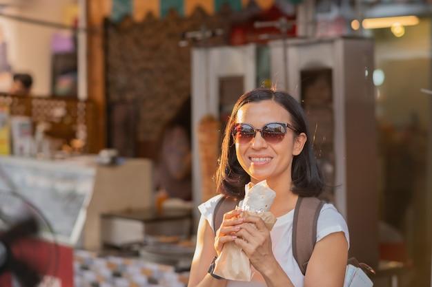 Heureuse femme mange un kebab de restauration rapide avec garniture dans la rue.