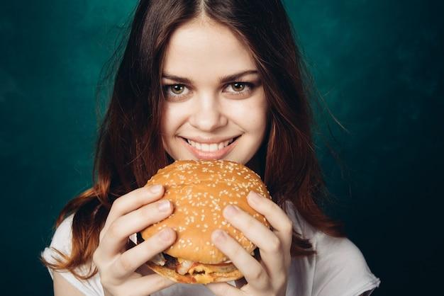 Heureuse femme mangeant un hamburger, studio