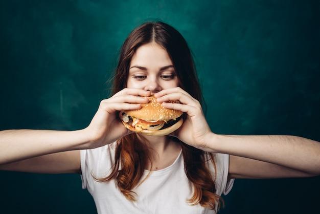 Heureuse femme mangeant un hamburger