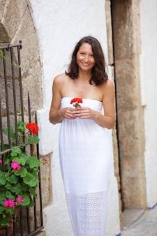 Heureuse femme marchant avec fleur en main