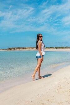 Heureuse femme marchant sur une plage tropicale.