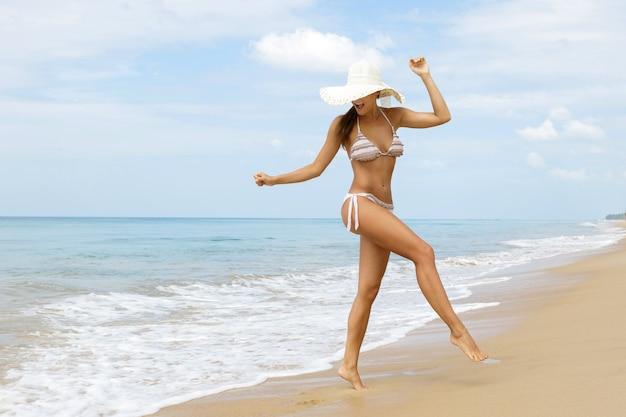 Heureuse femme marche sur la côte de la mer