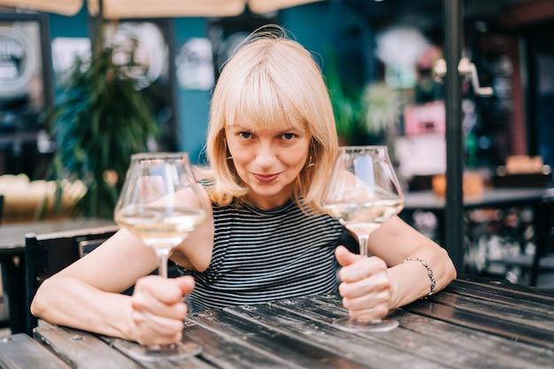 Heureuse femme mature adulte drôle assise dans un bar à l'extérieur et tenant des verres à vin dans un restaurant flou