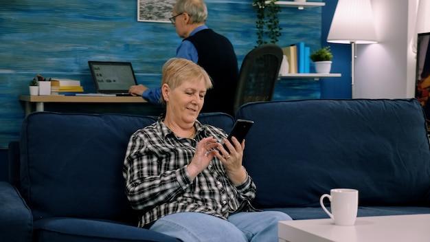 Heureuse femme mature d'âge moyen profitant de l'utilisation d'applications mobiles en tapant des messages texte s'asseoir sur un canapé