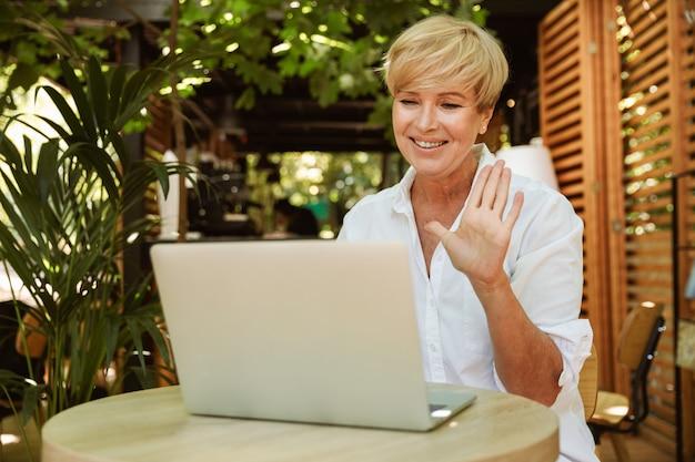 Heureuse femme mature assise dans un café avec ordinateur portable