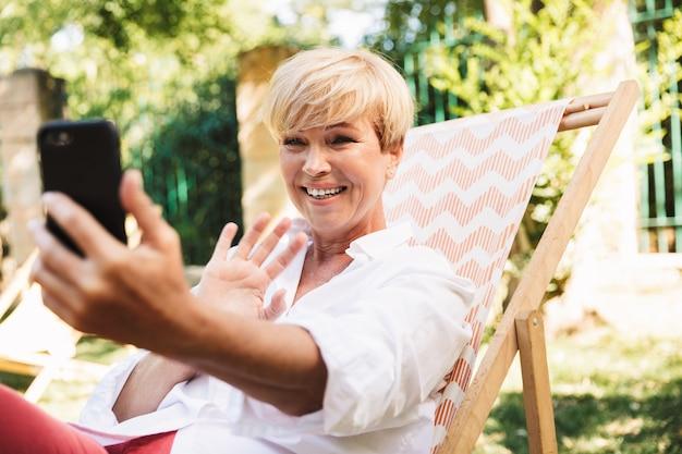 Heureuse femme mature ayant un chat vidéo