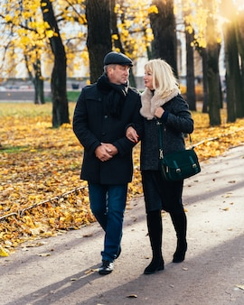Heureuse femme mature blonde et bel homme brune d'âge moyen à pied dans le parc