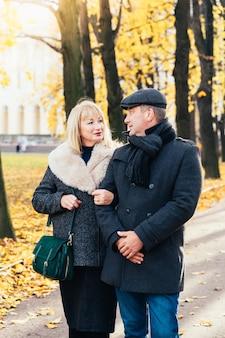 Heureuse femme mature blonde et bel homme brune d'âge moyen se promener dans le parc, se regardant