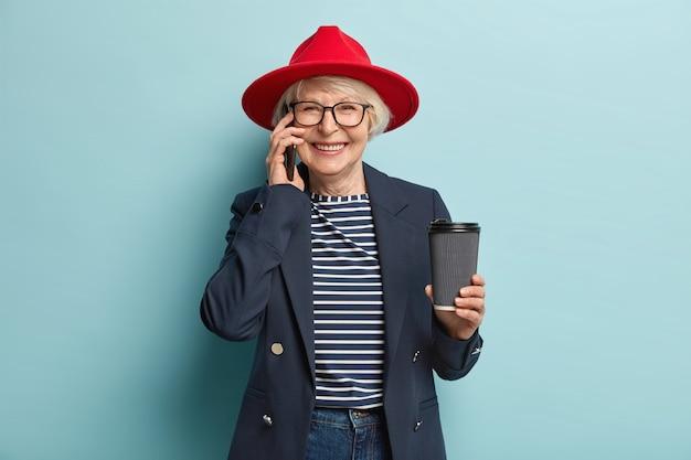 Heureuse femme mature a une conversation téléphonique agréable, utilise internet en itinérance pour la communication, fait un appel mobile, boit du café à emporter, porte des vêtements élégants, des modèles sur un mur bleu