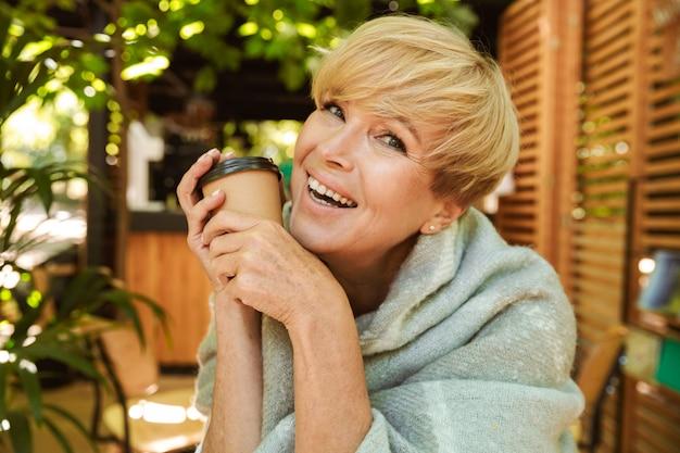 Heureuse femme mature enveloppée dans une couverture relaxante