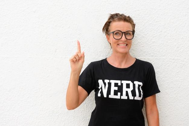 Heureuse femme mature nerd portant de grandes lunettes et debout isolé