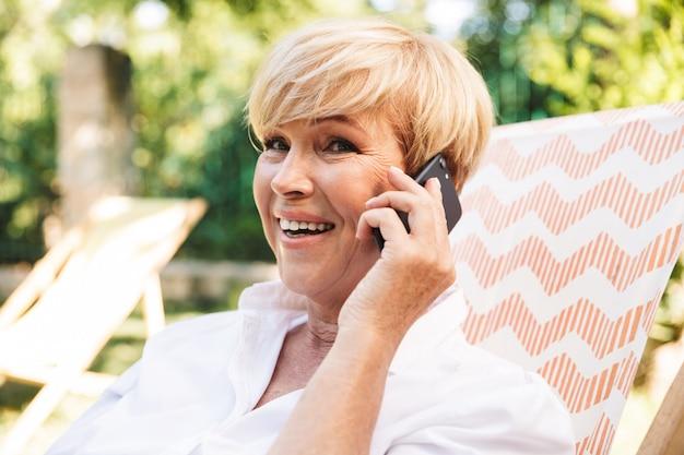 Heureuse femme mature parlant sur téléphone mobile