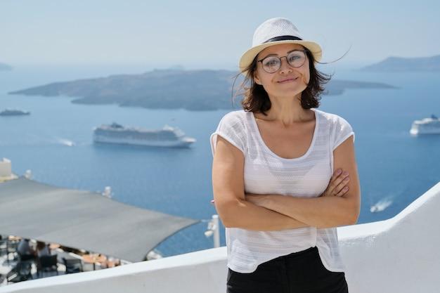 Heureuse femme mature touriste voyageant sur la célèbre île de santorin, femme avec les bras croisés regardant la caméra, arrière-plan mer, paquebots de croisière, ciel, espace pour copie