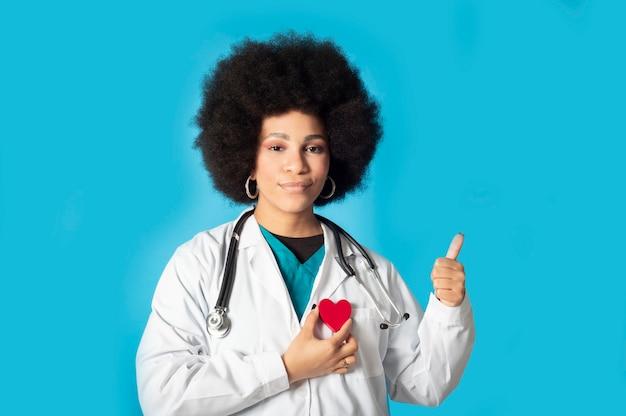 Heureuse femme médecin en uniforme tient un cœur avec ses mains tout en faisant un geste positif