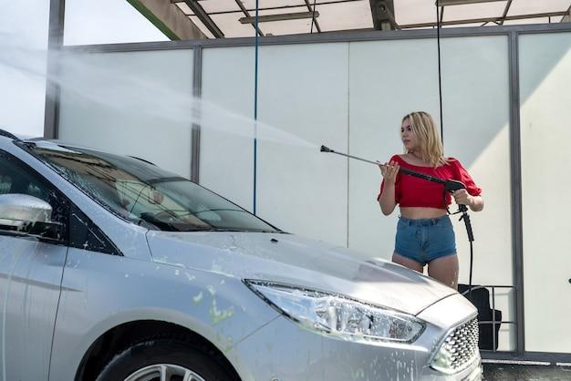 Heureuse femme mignonne nettoie sa voiture avec un pistolet à eau haute pression