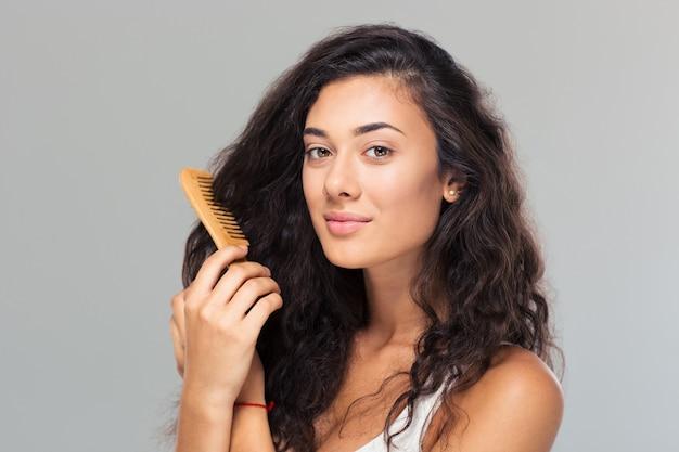 Heureuse femme mignonne se peignant les cheveux