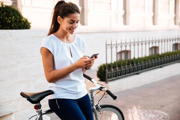 Heureuse femme mignonne tapant mesaage sur le smartphone s'appuyant sur un vélo dans la rue