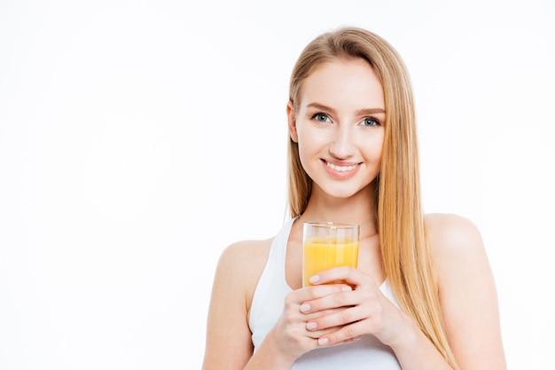 Heureuse femme mignonne tenant du jus d'orange frais isolé sur fond blanc