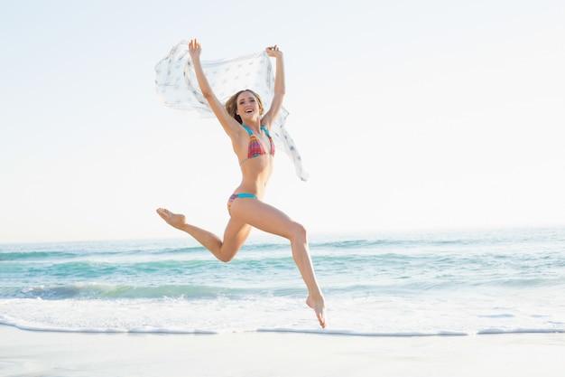 Heureuse femme mince sautant dans l'air en tenant le châle