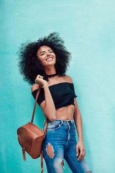 Heureuse femme mixte aux cheveux afro debout dans la rue