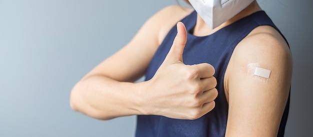 Heureuse femme montrant le pouce avec un bandage après avoir reçu le vaccin covid 19. vaccination, immunité collective, effet secondaire, efficacité, passeport vaccinal et pandémie de coronavirus