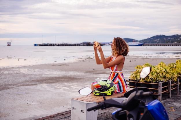 Heureuse femme de motard caucasien en robe d'été colorée en vacances avec casque de moto