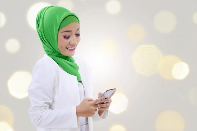 Heureuse femme musulmane asiatique tenant un téléphone